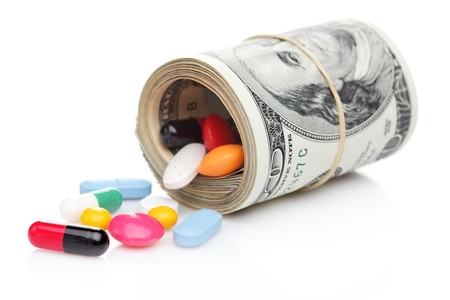 Money rolled up with pills flowing out isolated on white background, high costs of expensive medication concept photo