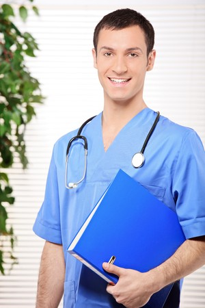 fascicule: Smiling healthcare professional holding a folder of patient or medical information in the office Stock Photo