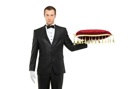 A man in a black suit holding a pillow isolated on white background
