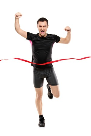 leotard: Full length portrait of a young runner at the finish line isolated on white background Stock Photo