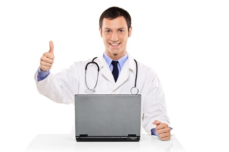 medical physician: A happy doctor with thumb up working on a laptop against white background Stock Photo