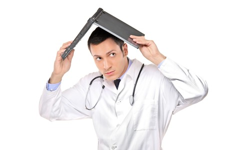 agitated: A scared young doctor covering his head with an open laptop isolated on white background Stock Photo