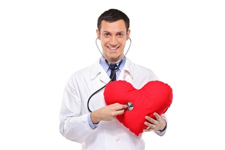 A smiling doctor examining a red heart shaped pillow with a stethoscope against white background Stock Photo - 8189572