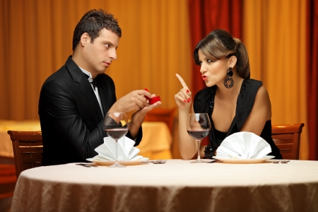 A young man making a proposal to his girlfriend in a restaurant Stock Photo - 8189634