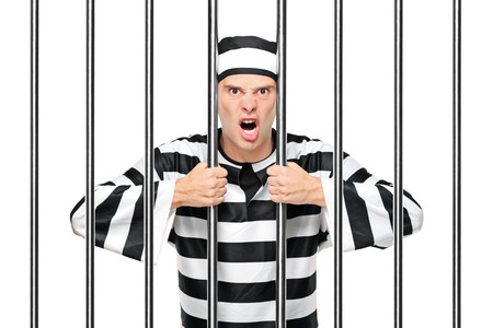 An agitated prisoner in jail holding bars isolated on white background photo