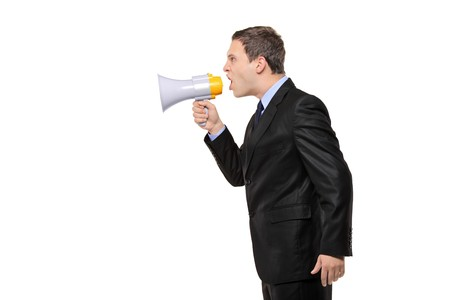 An angry businessman announcing via megaphone isolated against white background Stock Photo - 8189525