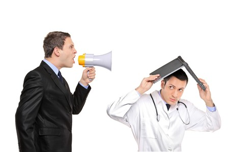 agitated: An angry businessman yelling via megaphone to a doctor isolated against white background Stock Photo