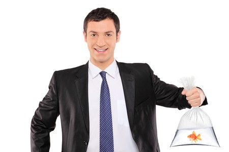 A smiling man holding a plastic bag with golden fish isolated on white background photo