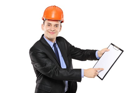 A young foreman wearing helmet and pointing on a clipboard isolated on white background photo