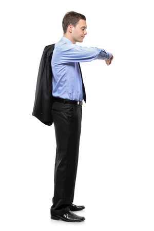 man waiting: Full length portrait of a man in a business suit standing and looking at his wrist watch isolated on white background Stock Photo