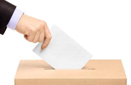 voting box: Mano mettendo un voto scrutinio in uno slot della casella isolato su sfondo bianco Archivio Fotografico
