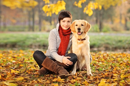 femme et chien: A beautiful woman and his dog (Labrador retriever) posing outside Banque d'images