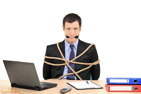 A businessman tied up with rope and gagged with band in the office isolated against white background photo