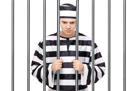 preso: Una vista de un triste preso en la c�rcel sosteniendo barras aisladas sobre fondo blanco Foto de archivo