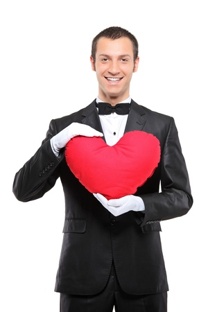 A happy man holding a red heart-shaped pillow isolated against white background Stock Photo - 8379748