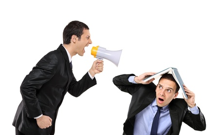 Angry businessman yelling via megaphone to a man who is covering his head with book Stock Photo - 8379749