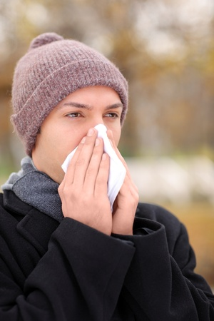 Infected man blowing his nose in tissue paper because of being ill Stock Photo - 8379753