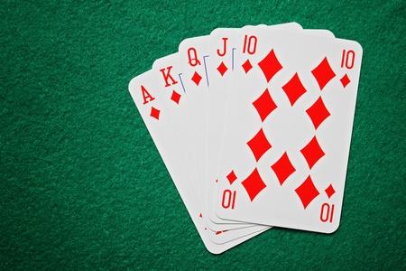 Royal straight flush poker cards on a green felt table background photo
