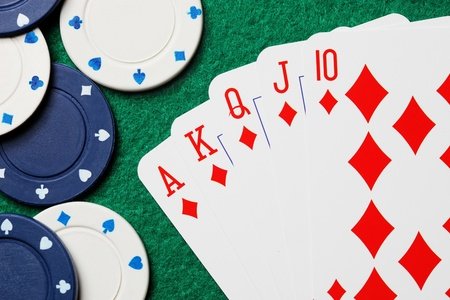 Royal straight flush poker cards with gambling chips on a green felt table background photo