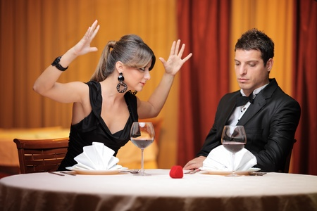 insulting: Young couple having an argument in a restaurant