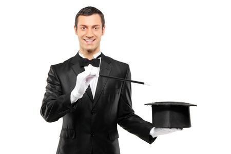 Un mago en un traje negro, sosteniendo un vacía de la chistera y Varita mágica aislados sobre fondo blanco