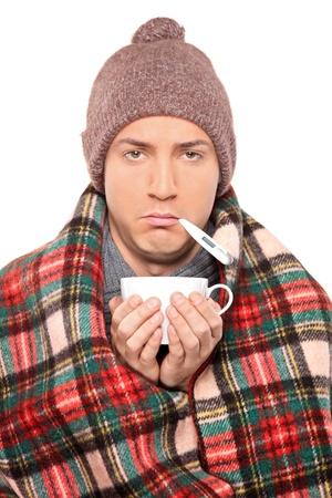 shiver: Ill man covered with blanket holding a tea cup and thermometer in his mouth isolated on white background Stock Photo