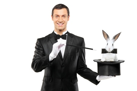 A magician in a black suit holding a top hat with a rabbit in it isolated on white background photo