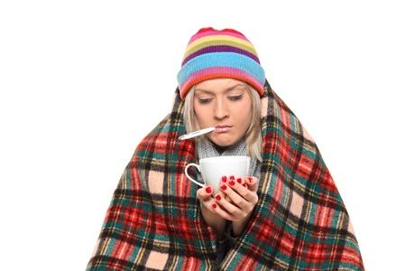gripe: Mujer enferma cubiertos con manta sosteniendo una taza de t� y un term�metro en su boca aislado sobre fondo blanco