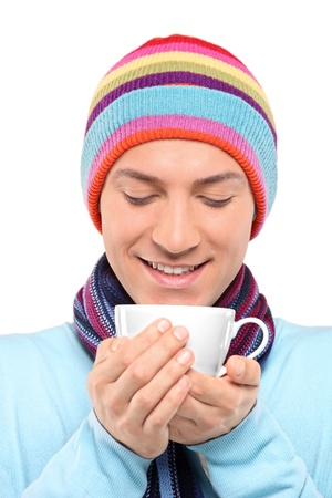 A smiling man wearing a hat and scarf holding a cup of tea isolated on white background Stock Photo - 8505744