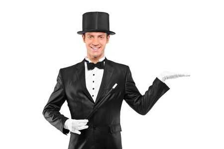 A view of a magician wearing top hat with raised left hand isolated on white background photo