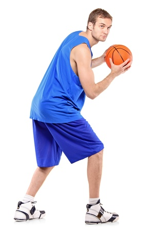 Full length portrait of a basketball player posing with a ball isolated against white background photo