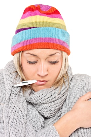 Ill woman wearing a cap and scarf with thermometer in her mouth isolated on white background photo