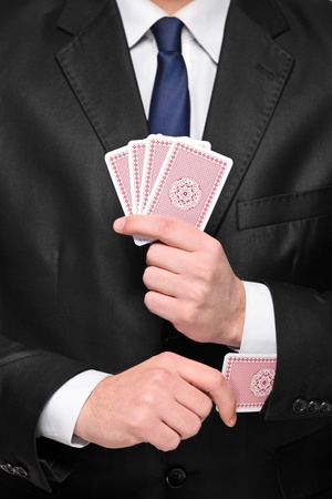 Person holding four cards in his hand and pulling one card from his sleeve photo