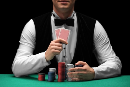 poker game: A man with bow tie holding cards and gambling chips Stock Photo