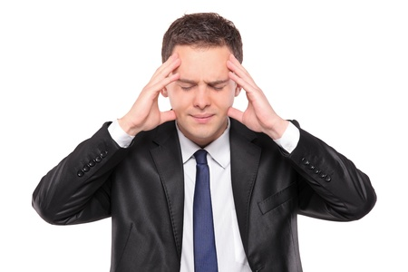 A man holding his head in pain as a result of a headache isolated on white background photo