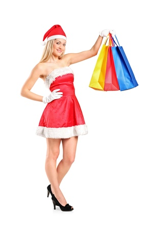 Full length portrait of a beautiful young woman dressed as Santa with shopping bags isolated on white background photo