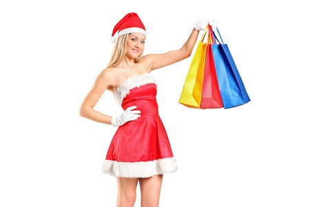Portrait of a beautiful young woman dressed as Santa with shopping bags isolated on white photo