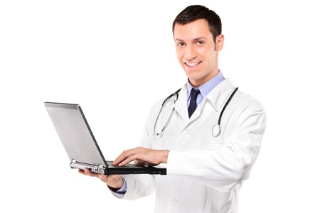 guy with laptop: Smiling doctor with stethoscope working on a laptop against white background