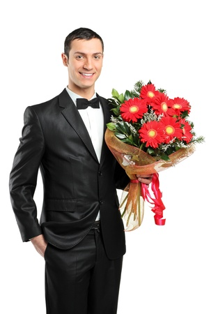suitor: A man holding out large bouquet of gerberas in formal black tux with bow tie isolated on white background