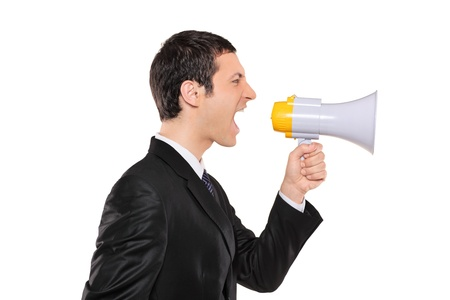 bawl: A displeased businessman in black suit shouting via megaphone isolated against white background Stock Photo