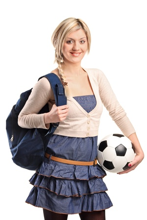 A female high school student wearing school bag and holding a football isolated on white background photo