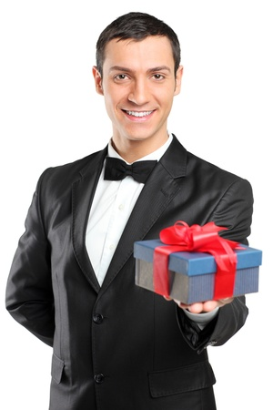 A smiling man in black suit and bow tie giving a gift isolated against white background