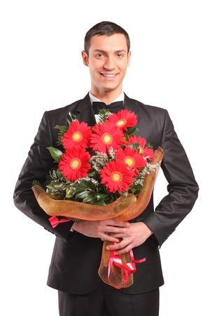 suitor: Maschio handsome indossando la tuta nera e farfallino detiene un bouquet di fiori isolato su sfondo bianco Archivio Fotografico