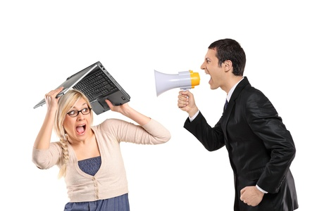 A mad businessman yelling via megaphone and woman covering his head isolated on white background photo