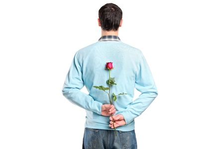 Man hiding a flower behind his back isolated on white background photo