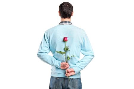 suitor: Uomo di nascondere un fiore dietro la schiena isolato su sfondo bianco