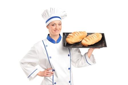 Smiling female baker showing freshly baked breads isolated on white background photo