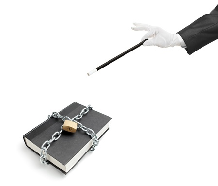 A magician holding a magic wand over a book with chain and padlock isolated on white background photo