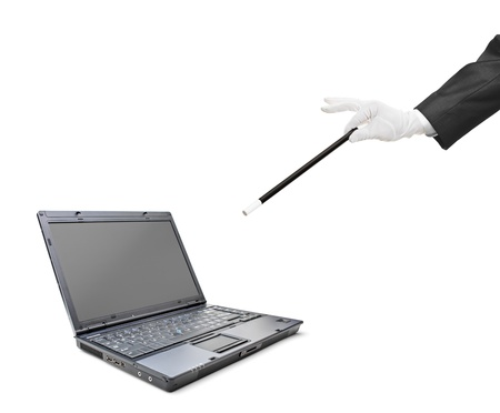 A magician holding a magic wand over a laptop isolated on white background photo