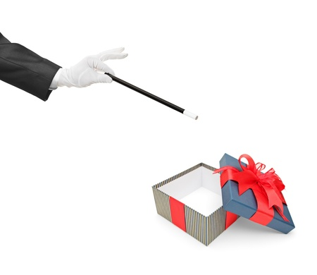 A magician holding a magic wand over an empty gift box isolated on white background photo